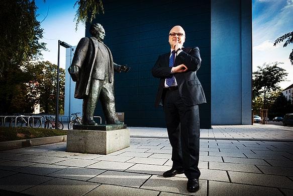 Armin Asper, Schulleiter des Martin-Andersen-Nexö-Gymnasium in Dresden, posiert vor seiner Schule neben der Statue von Martin Andersen Nexö.