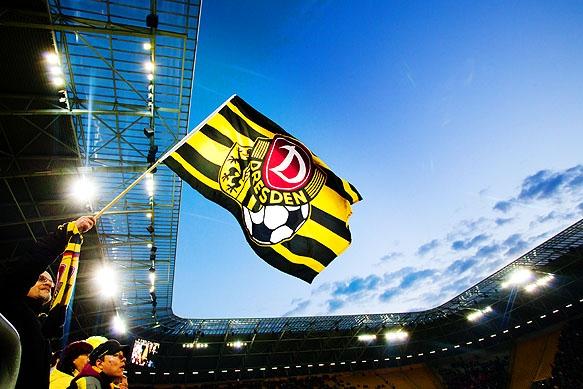 Dynamo Dresden Flagge vor Flutlicht und Abendhimmel
