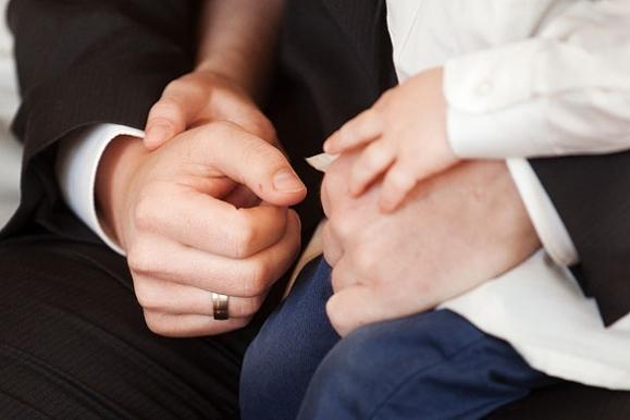 Hochzeitsfotograf - Hände des Bräutigams und des Nachwuchs